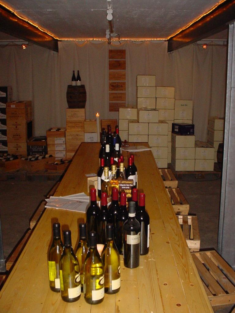 Lange proeftafel gevuld met flessen in een sfeervolle ruimte