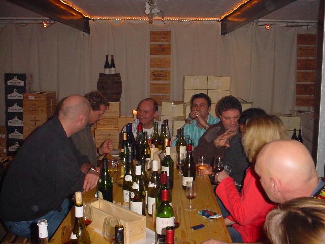Lange tafel gevuld met wijnproevenden mensen