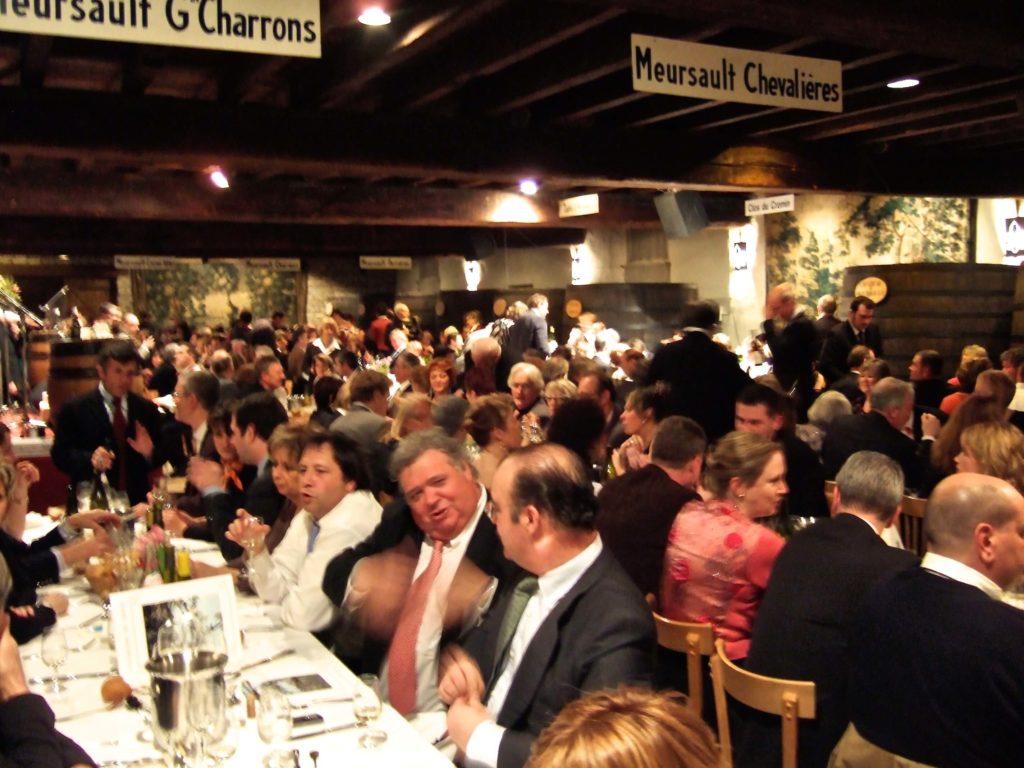 chique geklede mensen vieren feest aan lange tafels in de kelder van Château de Meursault tijdens de Bannée de Meursault