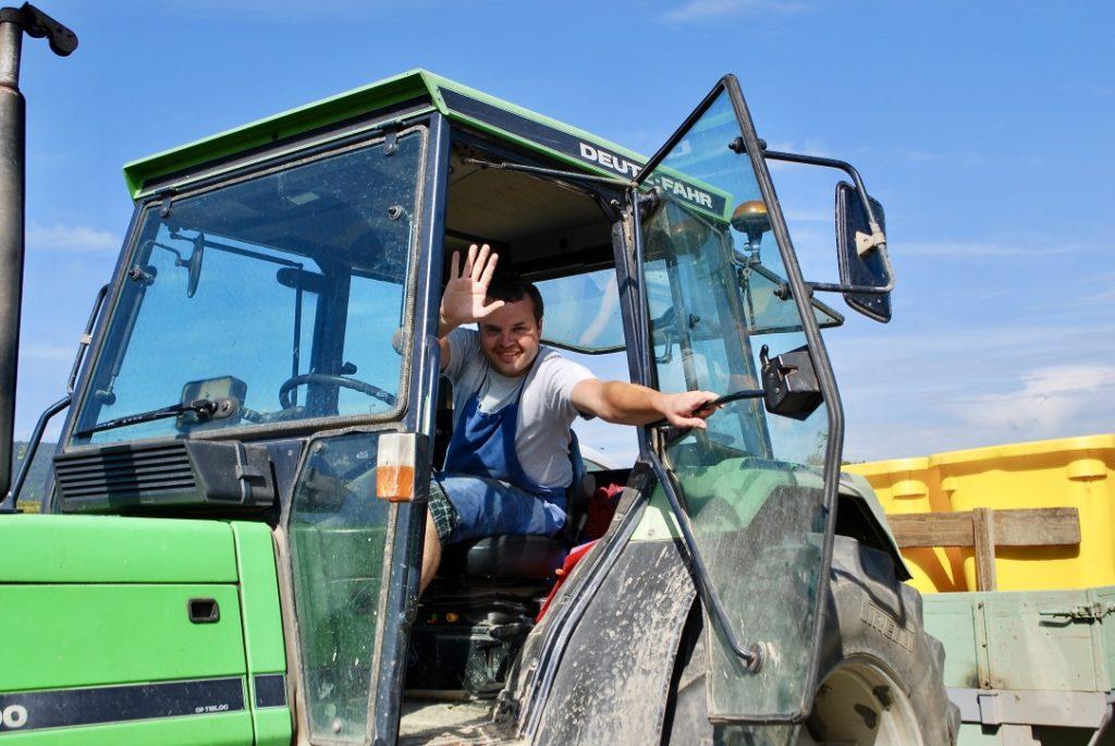 Arnaud Baur op de traktor. Hij opent zijn deur en zwaait naar ons.