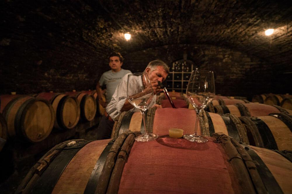 Jean Michel Gaunoux neemt een beetje wijn uit een wijnfust met een speciaal daarvoor ontworpen pipet