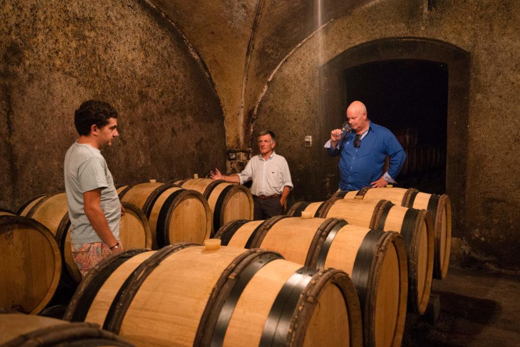 Jean Michel Gaunoux, zijn zoon en Arend Jan de Wijnman proeven wijn uit het vat in de kelder van Jean Michel