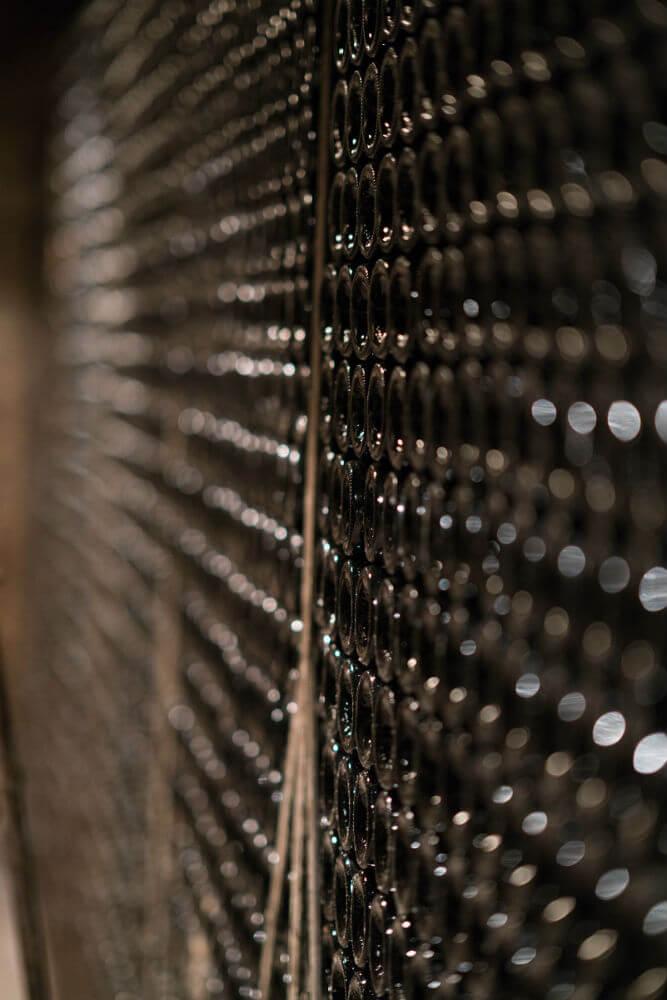 rijen met wijnflessen opgeslagen in de kelders van Jean Michel Gaunoux