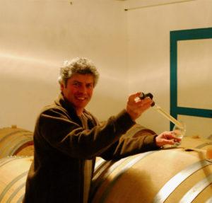 Alain Cailbourdin neemt een wijnmonster uit een houten vat