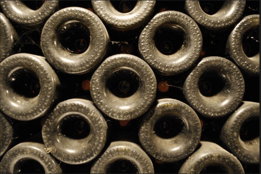 de bodems van gestapelde wijnflessen in de kelder van Jean Michel Gaunoux