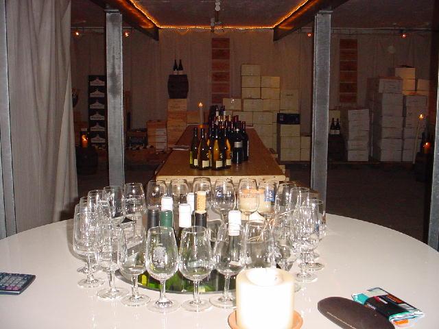 Ronde proeftafel gevuld met glazen en de lange proeftafel gevuld met flessen op de achtergrond
