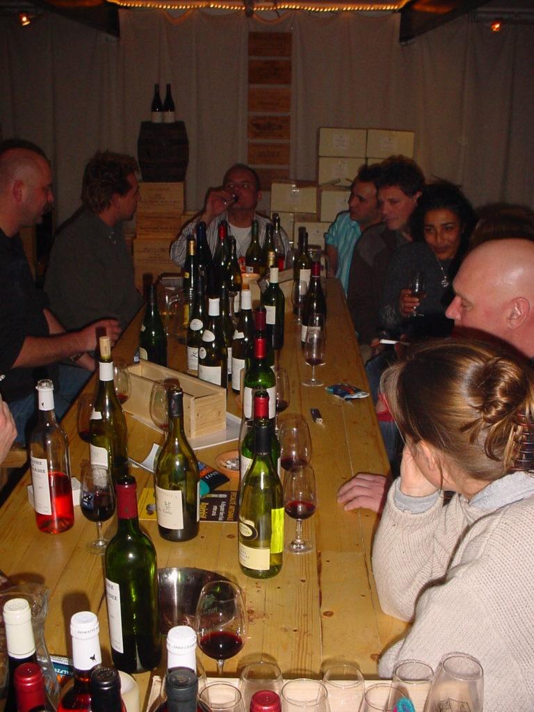gasten aan de lange proeftafel in de kelder