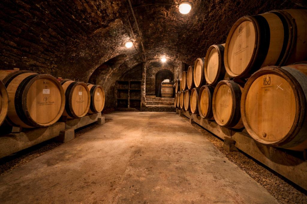 de wijnkelder van domain des Varoilles met gestapelde houten wijnvaten waar de wijn in rijpt