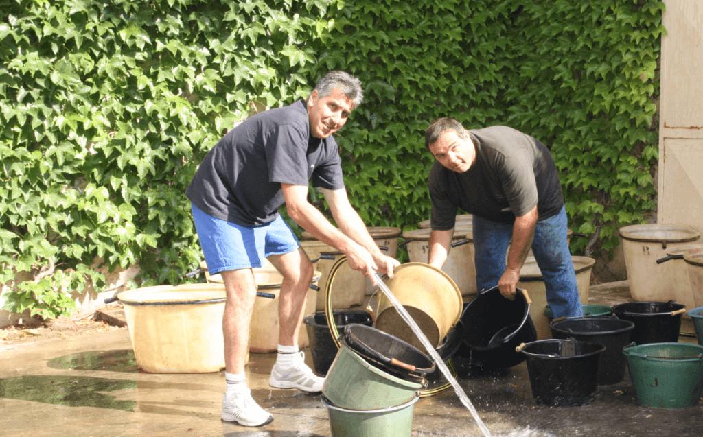 de mannen van les filles de Septembre spuiten de emmers waar de geoogste druiven in worden verzameld schoon