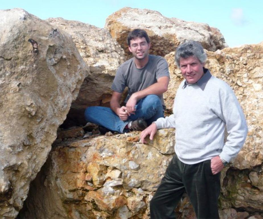 Loïc en Alain Cailbourdin poseren bij de grote uitgegraven rotsen