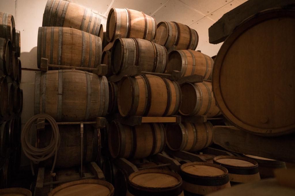 gestapelde eikenhouten wijnvaten in de kelders van de gebroeders Dampt