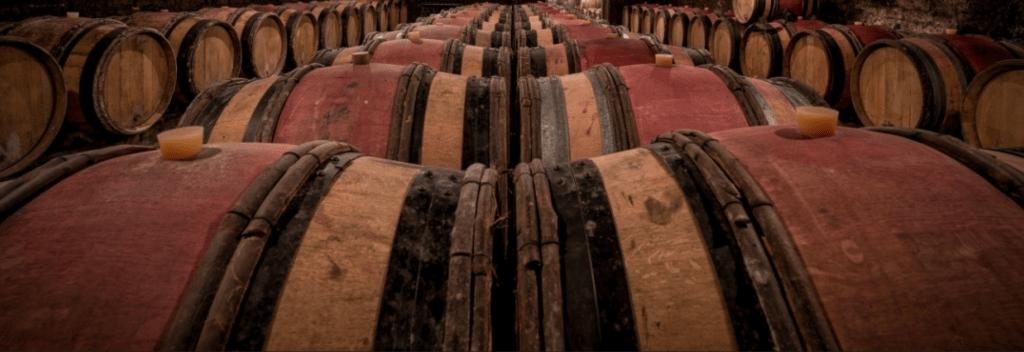 Eiken wijnvaten met rode wijnvlekken in een kelder